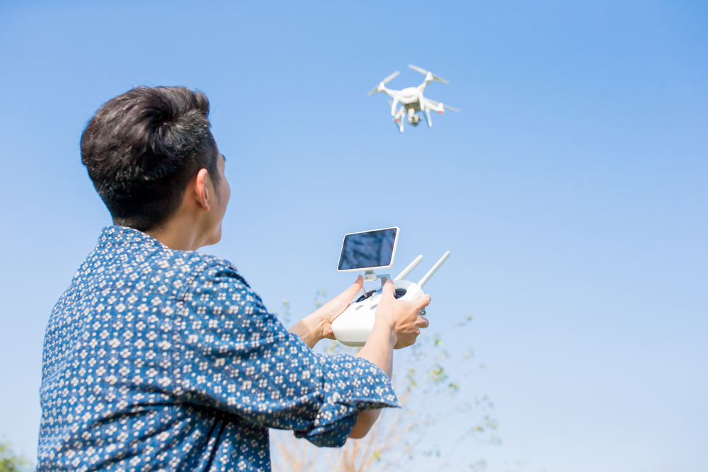 Drone pilot flying a drone outside.